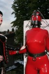 Pupett restrained in red latex catsuit