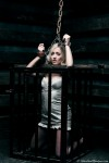 Slave Kerri caged and restrained with wooden stocks