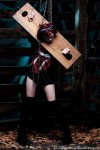 Punk rock chick restrained with heavy wooden stocks